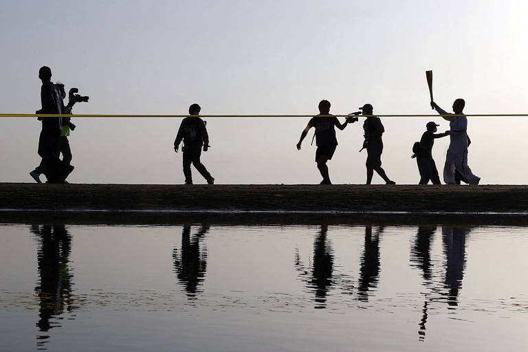 Foto mostra apenas os contornos das pessoas em um barco, onde um participante corre com a tocha em mãos