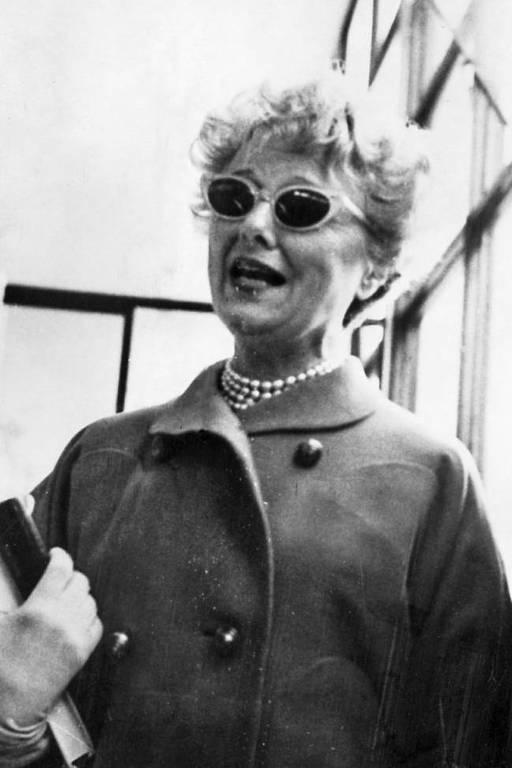 retrato em preto e branco de mulher com óculos escuros e colar de pérolas em saguão de aeroporto