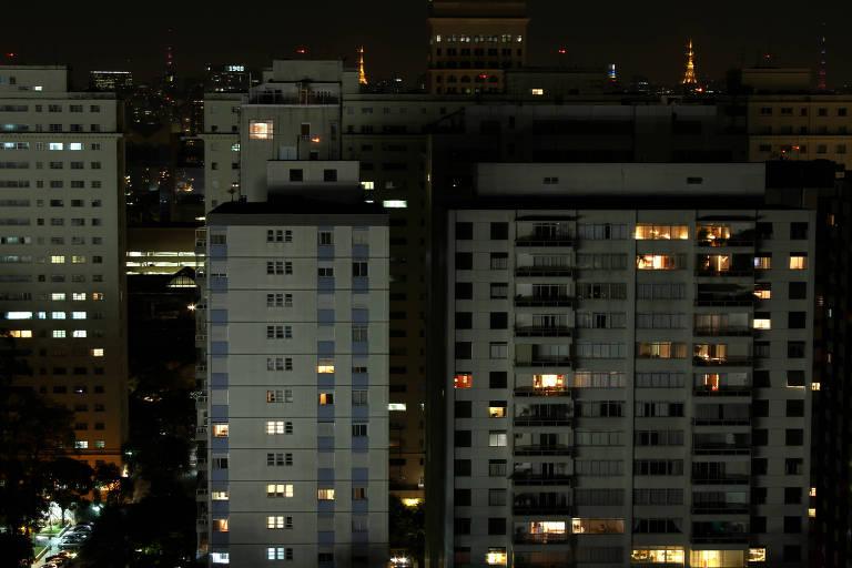 Paisagem de São Paulo durante a noite, com prédios com janelas acesas e torre iluminada ao fundo