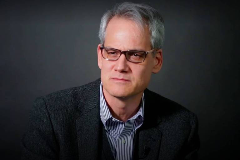 Homem branco de cabelo grisalho e óculos de grau usa terno preto