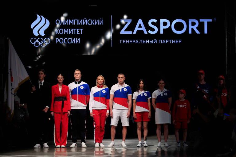 Pessoas perfiladas em passarela com uniformes nas cores azul, vermelha e branca