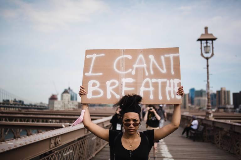 """Mulher segura cartaz com a frase """"Eu não posso respirar"""""""