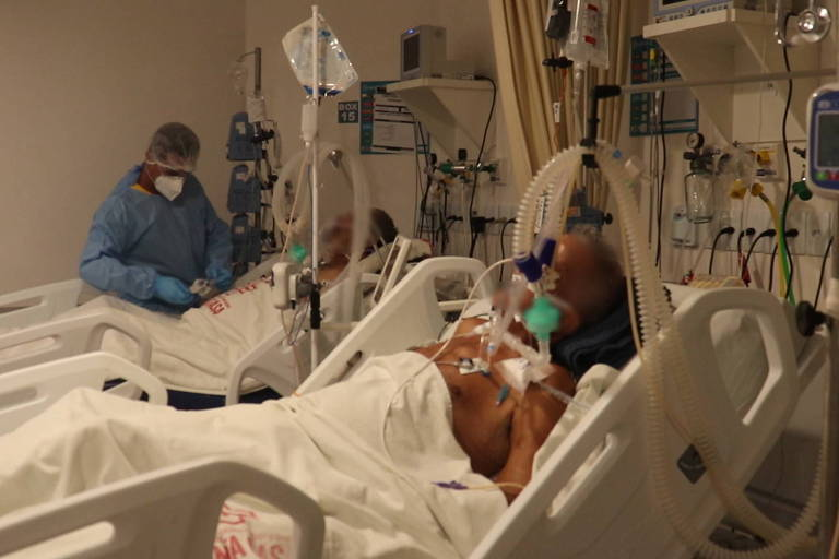 profissional de saúde com avental azul perto de uma das duas UTIs, com pacientes acamados