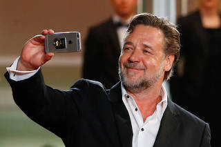 Cast member Russell Crowe uses a smartphone while arriving on the red carpet for the screening of the film