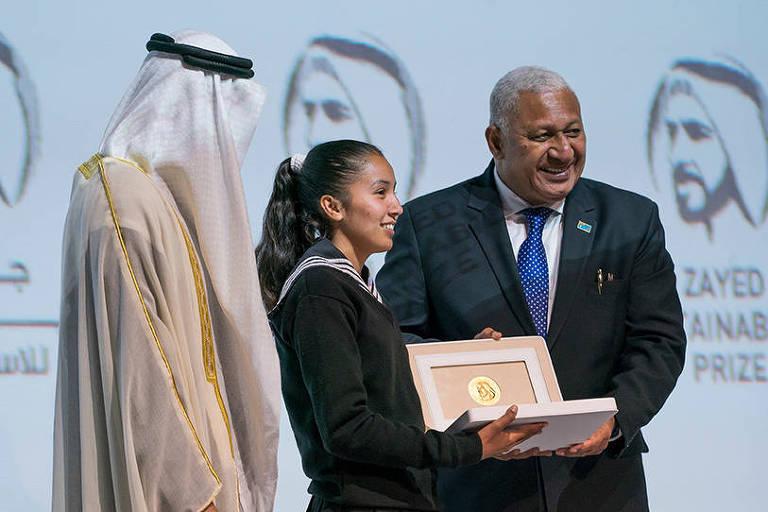 dois homens entregam troféu a uma jovem