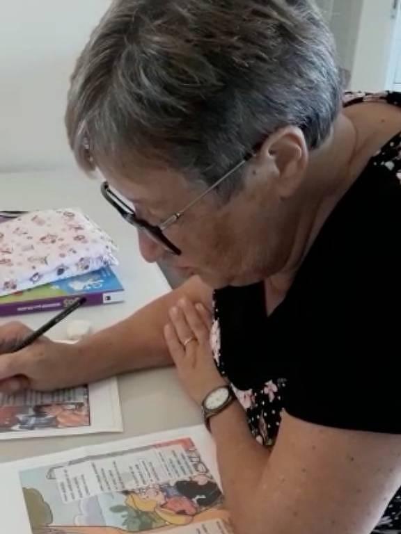 mulher idosa lê livro com lápis