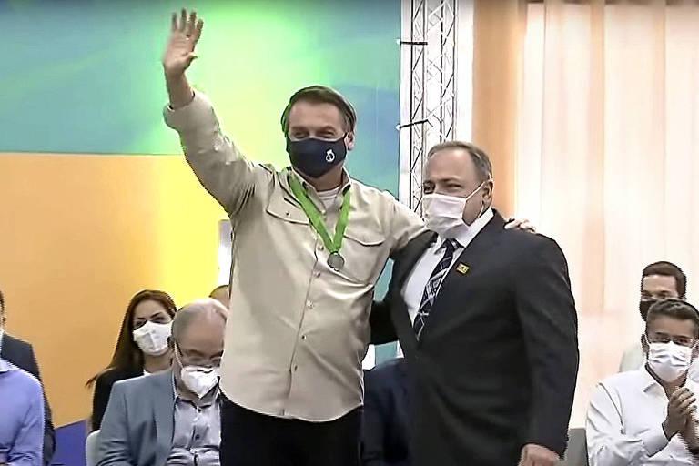 O presidente Jair Bolsonaro acena ao lado do ex-ministro da Saude Eduardo Pazuello durante a cerimônia de inauguração da Ferrovia Norte-Sul, trecho São Simão/GO
