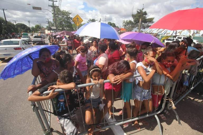 Grupo de pessoas dentro de cercadinho aglomerado com guarda-chuvas