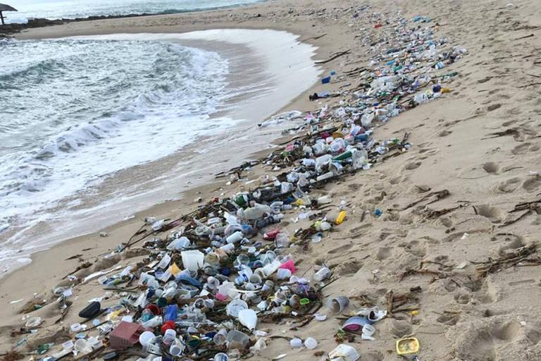 Faixa de areia onde a onda bate cheia de lixo
