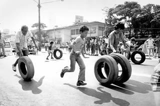 Crianças e adultos fazem corrida de pneus na avenida Nove de Julho, em São Paulo