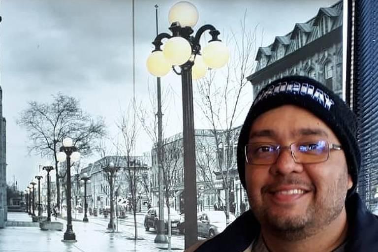 Luiz Fernando veste jaqueta marrom e touca preta e usa óculos. Ao fundo, aparece uma paisagem de frio.