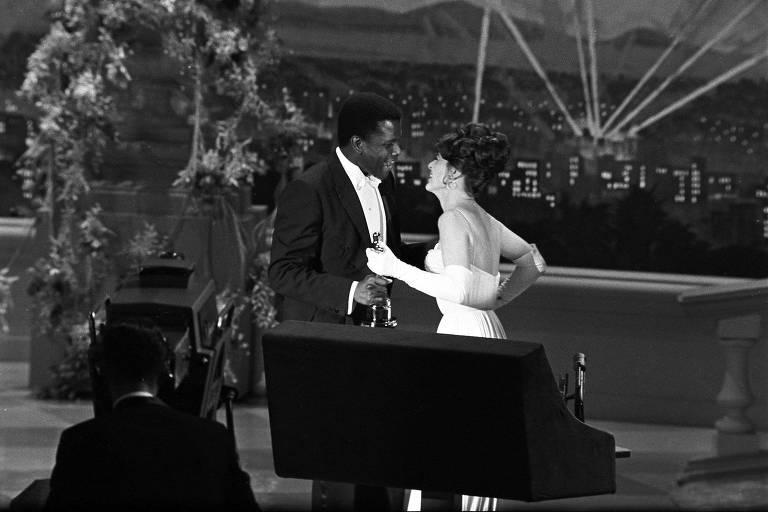 Sidney Poitier recebe o Oscar de melhor ator e é cumprimentado pela atriz Anne Bancroft em 1964
