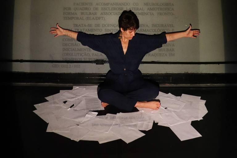 Mulher está sentada em palco escuro com os braços abertos, cercada por folhas de papel