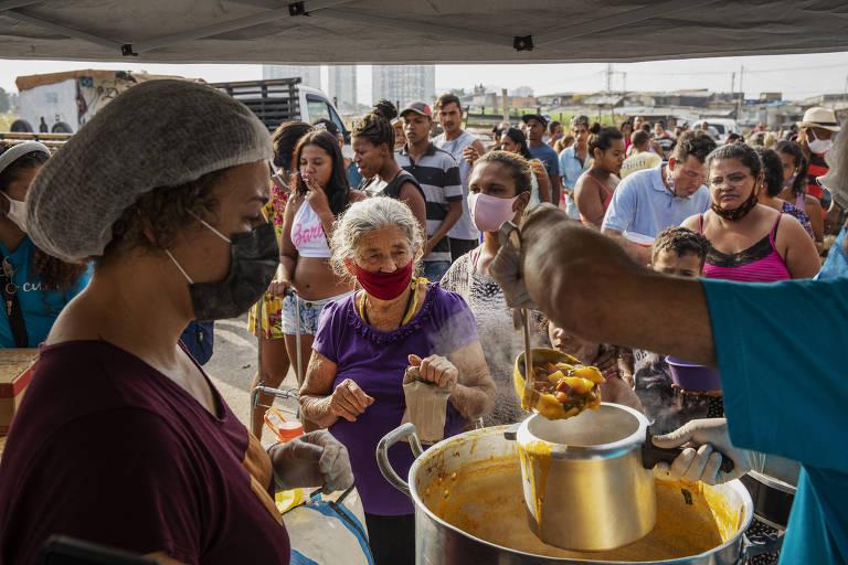 Moradores do Jardim Julieta, uma ocupação na zona norte de São Paulo que se formou em 2020, fazem fila para receber sopa distribuída por uma ONG