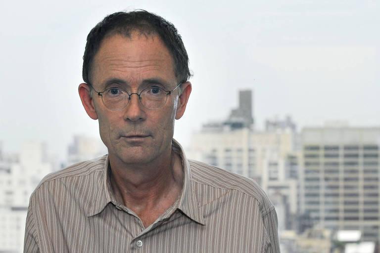 Homem de óculos e camisa listrada posa com o rosto sério e com cidade ao fundo