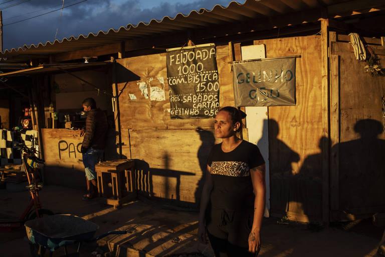 Uma mulher olha para o horizonte; seu rosto está iluminado pelo sol forte da tarde