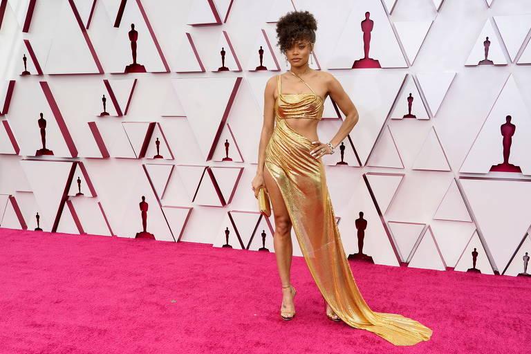 A atriz Andra Day no tapete vermelho com vestido dourado