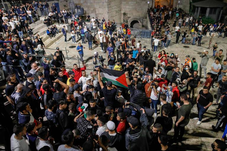 Aglomeração de pessoas em escadaria com bandeira palestina estendida