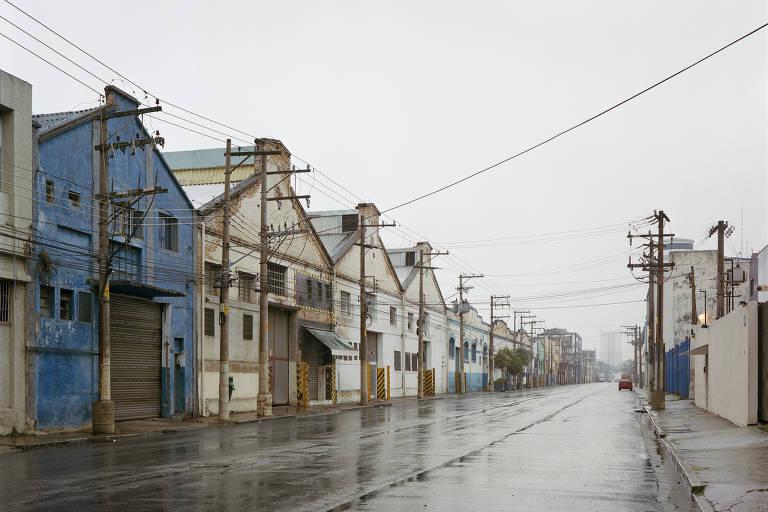 Rua que tem do lado esquerdo antigos galpões industriais, típicos da Mooca, pintados de cores diferentes