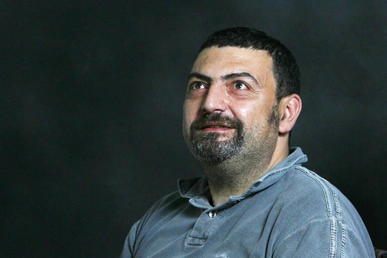homem branco, de rosto redondo e barba por fazer, sorri olhando para cima. ele veste uma camisa de jeans azul e está sentado