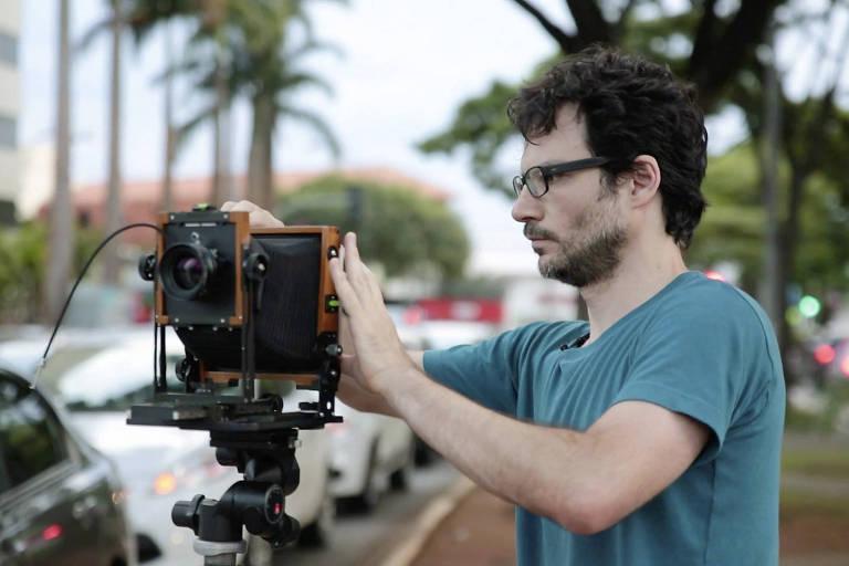 O fotógrafo está de perfil, de camiseta verde, ajustando sua câmera junto a uma rua com carros estacionados e, ao fundo, palmeiras