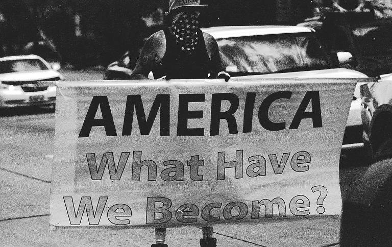 Homem com boné de Trump segura cartaz que diz 'América, o que nos tornamos?'