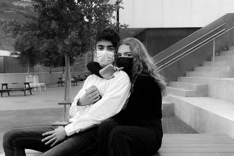 Casal abraçado, sentado em banco, vestindo máscaras cirúrgicas. Foto em preto e branco.