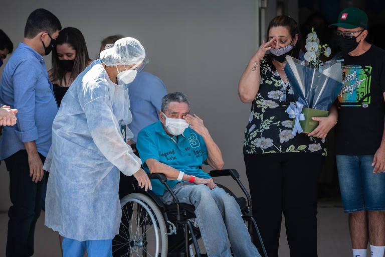 O último paciente Iray Fernandes sai de cadeira de rodas do hospital; ele é empurrado por uma pessoa de avental, touca e máscara. Ele e uma mulher em pé, ao lado dele, se emocionam, passando a mão no olho, enxugando lágrimas