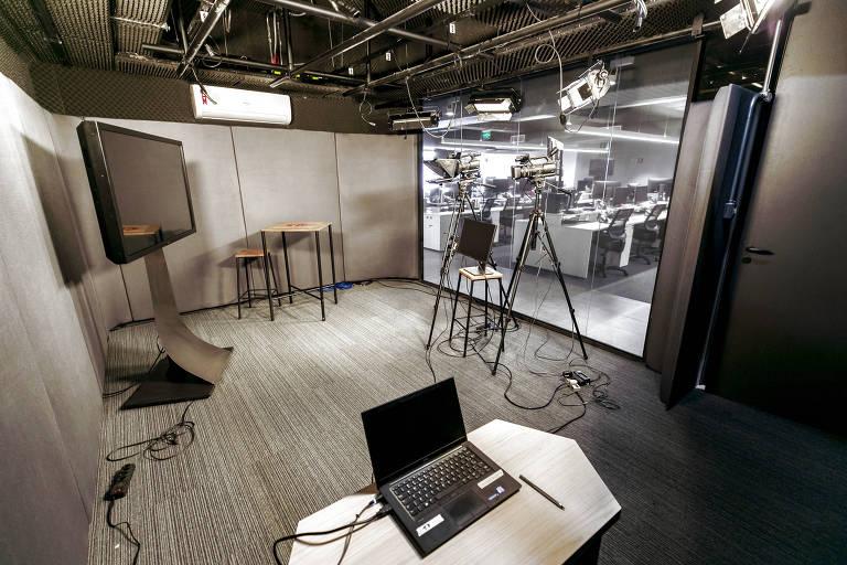 Sala com parede de vidro com duas câmeras, tv e notebook sobre uma mesa