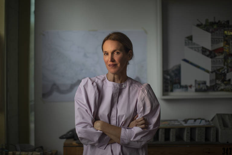 Retrato da arquiteta; é uma mulher de cabelo castanho claro, que posa com os braços cruzados na frente do peito; ela usa uma blusa bufante num tom lilás