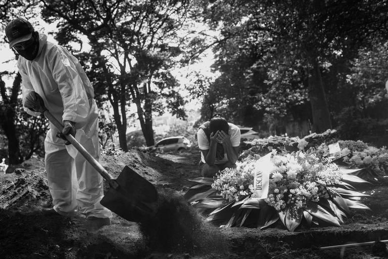 Sepultador joga terra sobre um caixão em cova; ao fundo, mulher ajoelhada no chão chora com as mãos no rosto