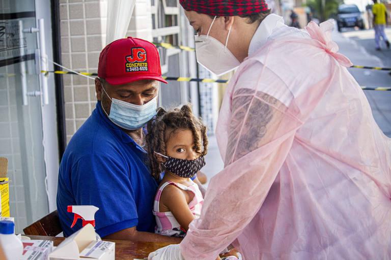 Homem de camiseta azul, boné vermelho e máscara azul segura menina no colo, enquanto à frente uma profissional de saúde, também de máscara, prepara materiais para testagem