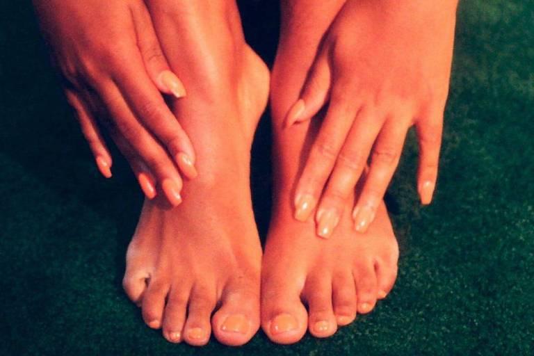 Mãos e pés brancos sobre veludo verde