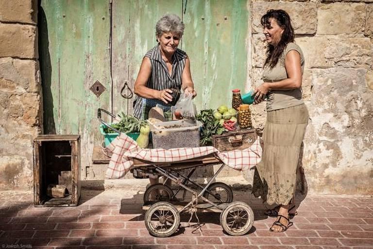 """""""Uma senhora vende alcaparras e outras iguarias de seu velho carrinho nas ruas de Marsaxlokk, uma vila de pescadores em Malta."""""""