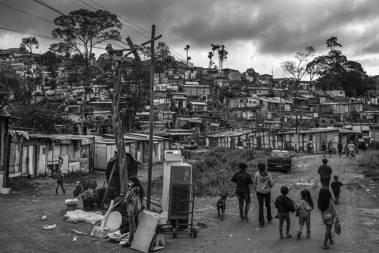 Pessoas são retratadas de costas enquanto caminham em direção a uma ocupação. Imagem em preto e branco.