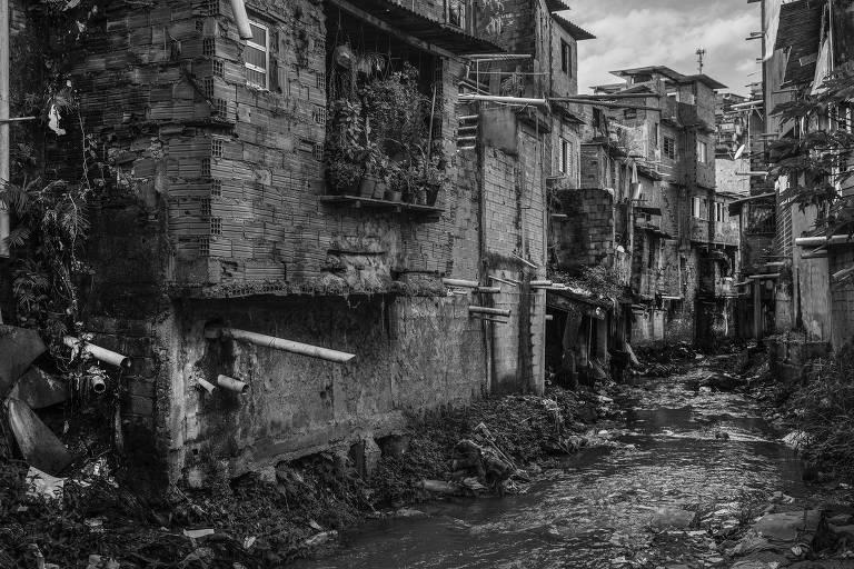 Canos ligados a casas despejando esgoto em córrego. Imagem em preto e branco.