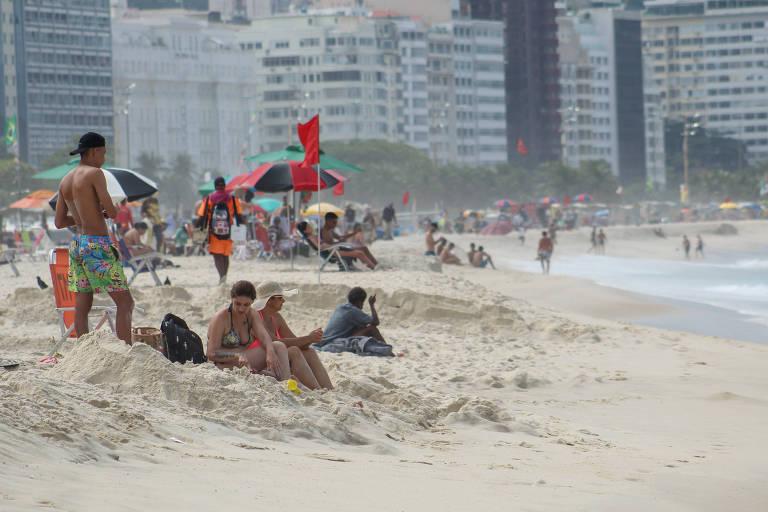 Pessoas sentadas e em pé na areia de praia com prédios ao fundo; é possível ver barracas, vendedor de biscoito Globo e muita gente na praia