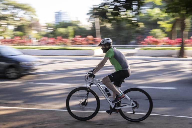 Homem de bermuda preta e camiseta verde e cinza, de capacete e máscara, pedala em rua com árvore ao fundo; no sentido contrário ao dele, está um carro, no cando esquerdo da foto. O fundo da imagem está desfocado