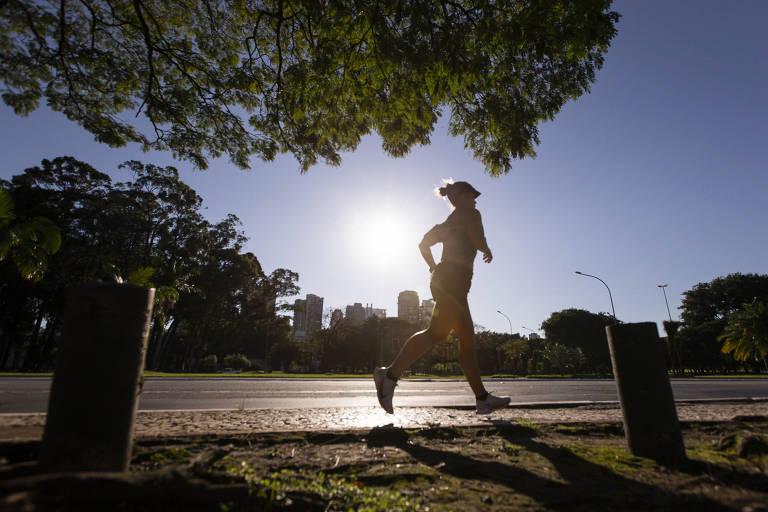 Pessoa corre em chão de asfalto em imagem contra o sol. No alto da foto, saindo do canto superior esquerdo até a metade, a copa de uma árvore