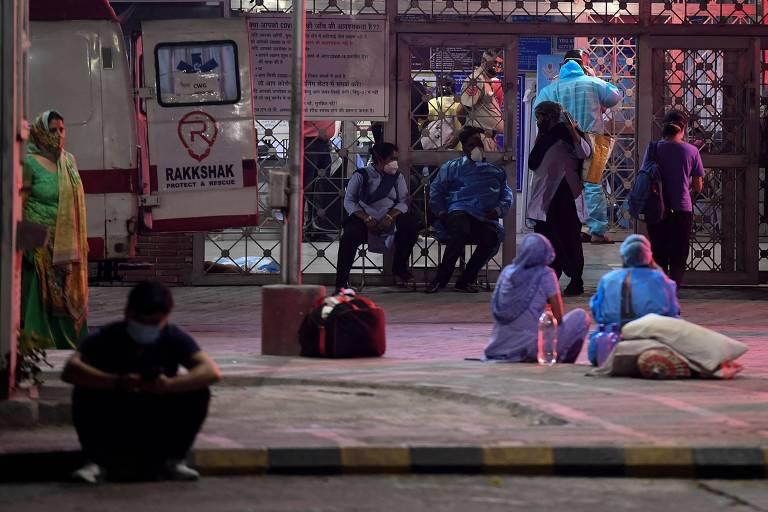 Parentes de vítimas de Covid aguardam do lado de fora do serviço de emergência do hospital Memorial Jawahar Lal Nehru, em Nova Déli, na Índia. Há duas mulheres sentadas na calçada e um homem sentado na sarjeta