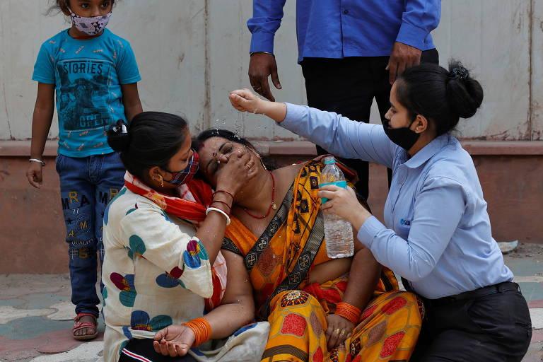 Mulher vestida de amarelo estampado está sentado no chão e é consolada por duas pessoas; atrás dela está uma criança de camiseta azul e um adulto