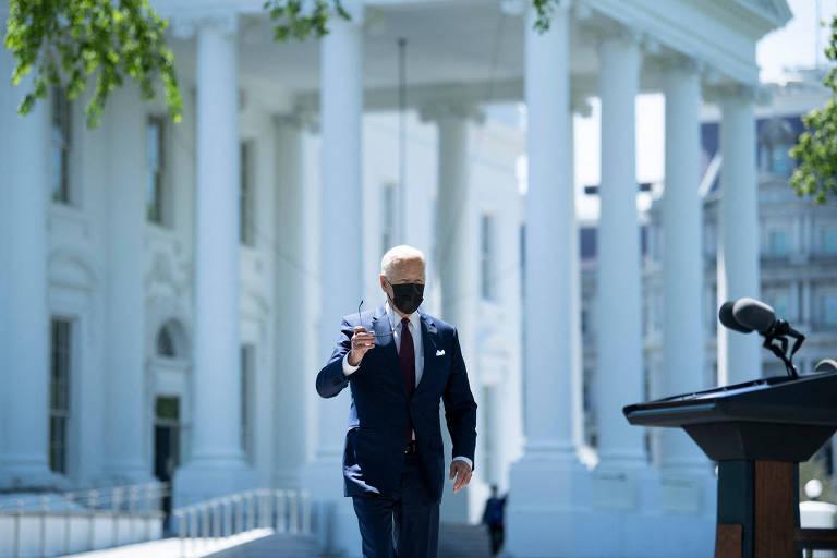 O presidente dos EUA, Joe Biden, tira os óculos escuros enquanto caminha para falar em entrevista coletiva em frente à Casa Branca