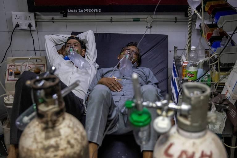Pacientes com Covid-19 compartilham leito para receber tratamento contr a a doença em hospital em Nova Déli