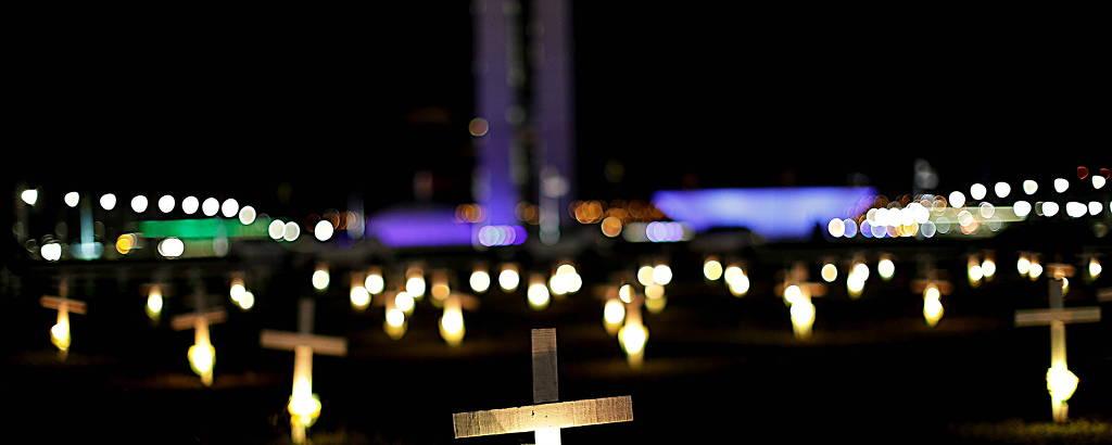 Velas e cruzes colocadas diante do Congresso Nacional, em Brasília, prestam homenagens às vítimas da Covid-19
