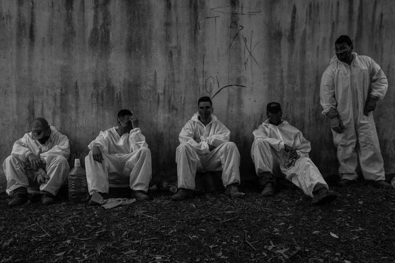 Cinco homens com roupas de proteção brancas, sentados no chão e encostados em uma parede branca e suja