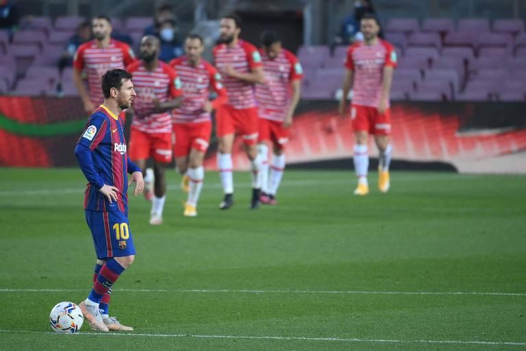 Lionel Messi olha desconsolado enquanto os jogadores do Granada comemoram o gol da vitória sobre o Barcelona, em pleno Camp Nou