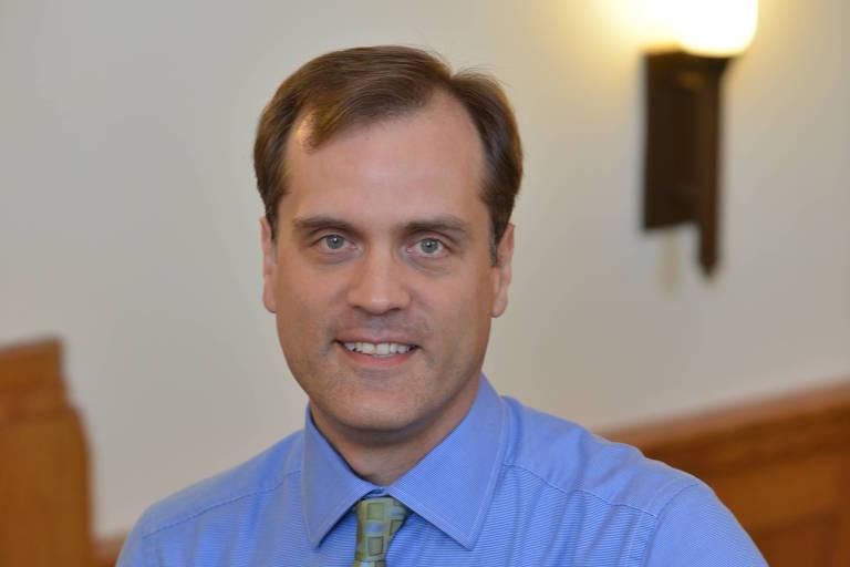 Retrato de homem branco com camisa azul e gravata