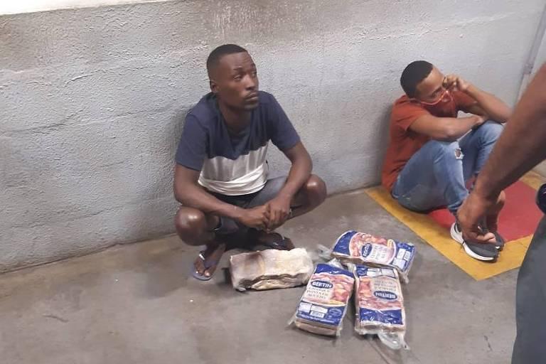 Dois homens estão sentados no chão, encostados em uma parede, com pactes espalhados à frente. No canto direito da foto, é possível ver a perna de uma pessoa de calça e sapato