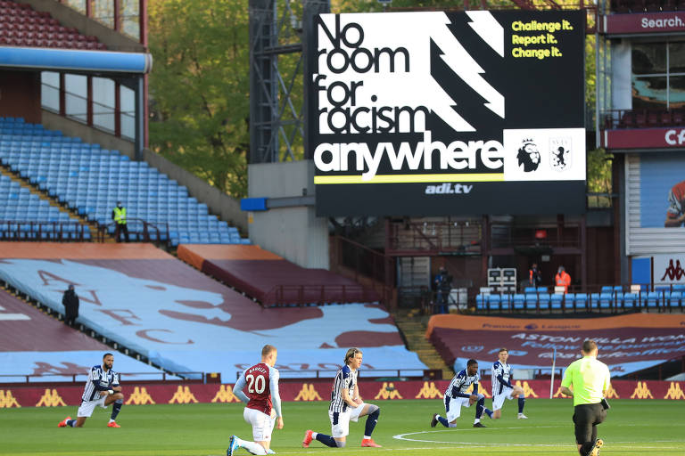 Telão mostra com mensagem enquanto jogadores se ajoelham em protesto