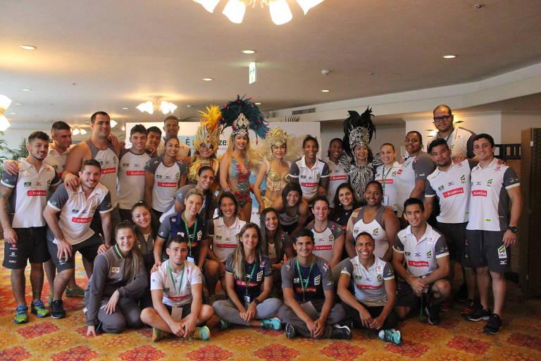 Grupo de atletas posa para foto com mulheres em trajes carnavalescos